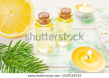The concept of aromatherapy, relaxation, organics. Transparent bottles with aromatic oil and sea salt, spruce branch, lemon, candles on a light wooden background. Organic Apothecary #1529518763