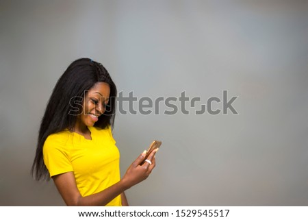 satisfied Young African hipster girl,types text message on cell phone, enjoys online communication, types feedback, wears yellow shirt, isolated on Gray studio wall. Technology concept #1529545517