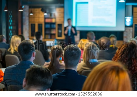 Audience listens lecturer at workshop in conference hall, rear view Royalty-Free Stock Photo #1529552036