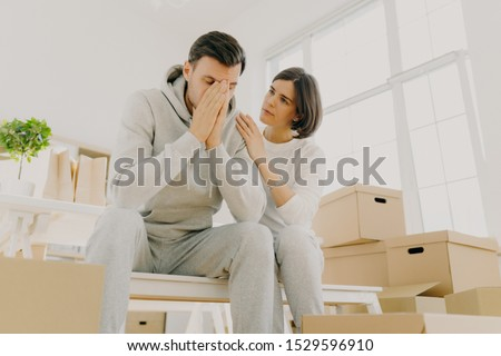 Photo of dissatisfied husband and wife forced to sell apartment because of financial problems, woman soothes husband, pose on cardboard boxes, pose in living room. Moving as kind of stress for family #1529596910