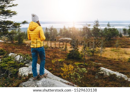 Woman traveler in yellow jacket from back hike in autumn forest in Finland Lapland. Hiking travel and adventure. #1529633138