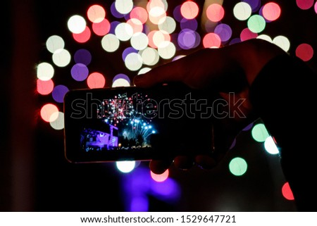Silhouette of hands with mobile cell phone to take a photo of fireworks