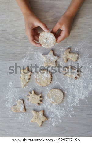 kids Little hands with handmade cookie on wooden table. Christmas gingerbreads, different shapes. #1529707196