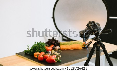 Food photography. Object shooting. Camera on tripod softbox organic vegetables on table.