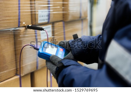 Hand of worker using thermometer to temperature measurement in the goods boxes with ready meals after import in the cold room or warehouse for keep temperature room Royalty-Free Stock Photo #1529769695
