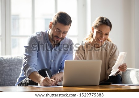 Happy couple using laptop, calculating domestic bills, mortgage or loan documents, smiling woman holding papers, family planning budget, managing household expenses, focused man filling form Royalty-Free Stock Photo #1529775383