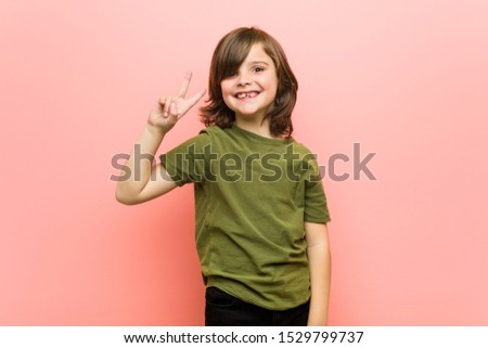 Little boy joyful and carefree showing a peace symbol with fingers. #1529799737
