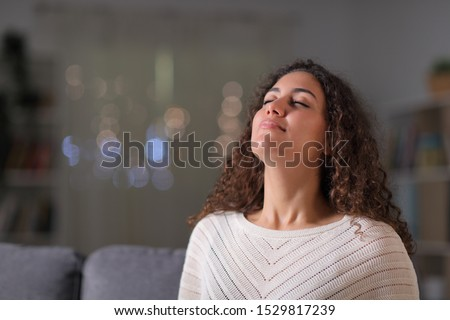 Relaxed arab woman breathing fresh air sitting on a couch in the living room in the night at home Royalty-Free Stock Photo #1529817239