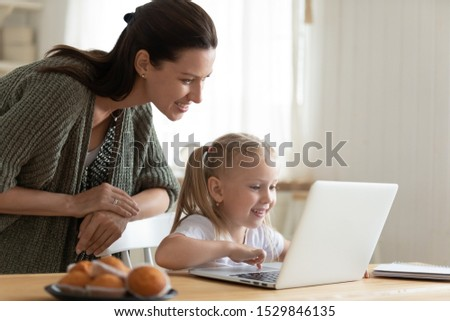 Smiling mother and little daughter using laptop, looking at screen, sitting at table in kitchen, playing or shopping online together, happy mum and adorable child having fun with computer #1529846135