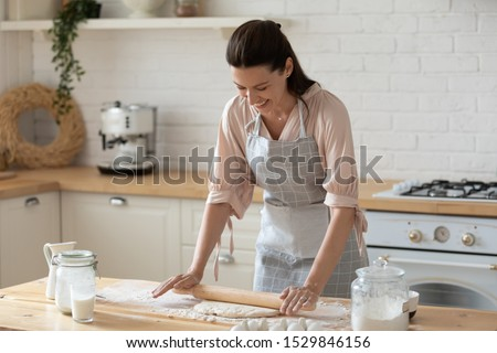 Smiling young woman wearing apron rolling out dough with rolling pin in hands, happy female preparing breakfast, baker cooking cake or cookies in kitchen at home, standing at table #1529846156