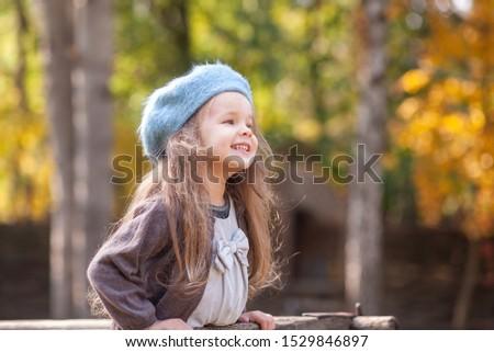 Portrait of a beautiful little girl in a blue beret. A child walks in a beautiful autumn park. #1529846897