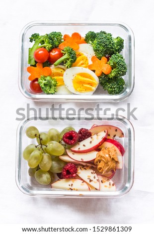Healthy diet snack, breakfast lunch box on light background, top view. Boiled egg, fresh vegetables and fruits - tasty healthy food concept    #1529861309