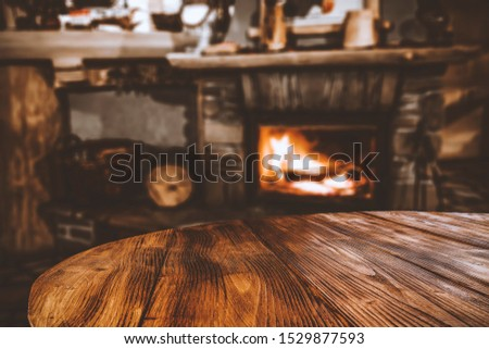 Mood photo of dark wooden table with free space for your decoration and blurred background of friepalce