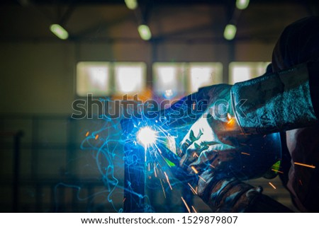 A man in protective clothing welding metal parts #1529879807