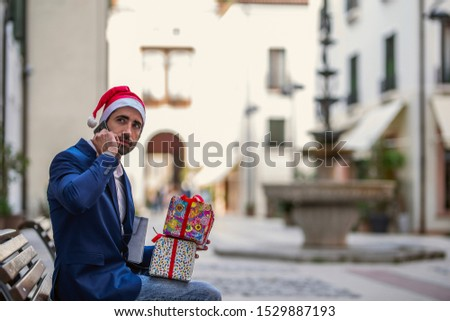 Beautiful young man on the phone wearing a casual suit, sitting on a bench with gifts. #1529887193