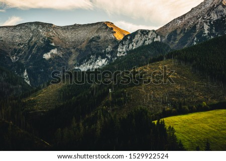 High rocky mountains against the background of the setting sun. Zdiar in Slovakia, high Bielanske Tatras. Trip to the mountains, climbing, hiking in the mountains. Tourists in the mountains. #1529922524