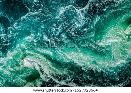 Waves of water of the river and the sea meet each other during high tide and low tide. Whirlpools of the maelstrom of Saltstraumen, Nordland, Norway Royalty-Free Stock Photo #1529923664