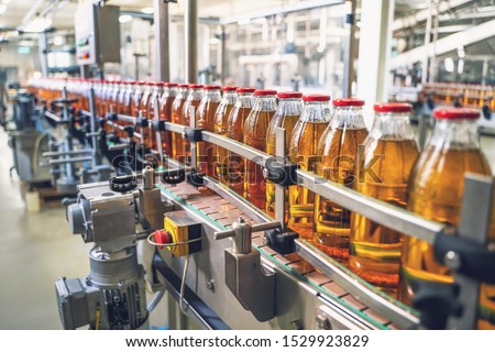 Conveyor belt, juice in glass bottles on beverage plant or factory interior, industrial manufacturing production line, toned Royalty-Free Stock Photo #1529923829