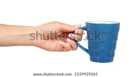 Hand with blue ceramic cup, mug for coffee and tea, kitchen pottery. Isolated on white background. #1529929265