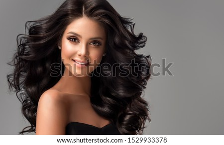 Beauty brunette girl with long  and   shiny wavy black hair .  Beautiful   woman model with curly hairstyle . #1529933378
