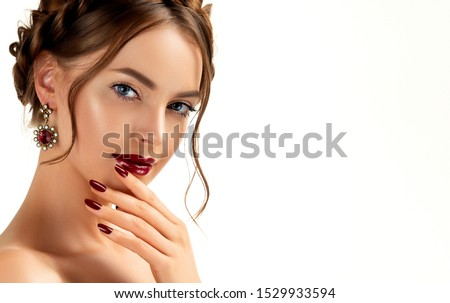 Beautiful model girl with burgundy or wine color manicure on nails . Fashion makeup and cosmetics . Jewelry, earrings and accessories. Beauty woman with braid hairstyle around her head.  #1529933594