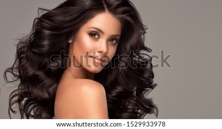 Beauty brunette girl with long  and   shiny wavy black hair .  Beautiful   woman model with curly hairstyle . #1529933978