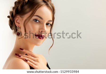 Beautiful model girl with burgundy or wine color manicure on nails . Fashion makeup and cosmetics . Jewelry, earrings and accessories. Beauty woman with braid hairstyle around her head.  #1529933984