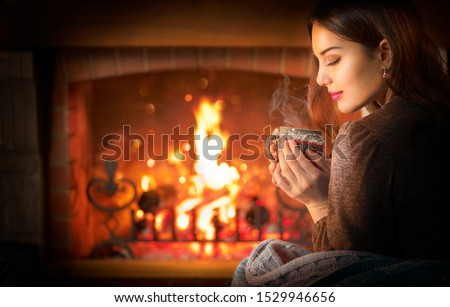 Beauty young Christmas woman sitting near fireplace in dark room at home and drinking hot beverage from a big cup. Beauty girl Enjoying tea, coffee or hot chocolate in a cozy room. Xmas scene #1529946656