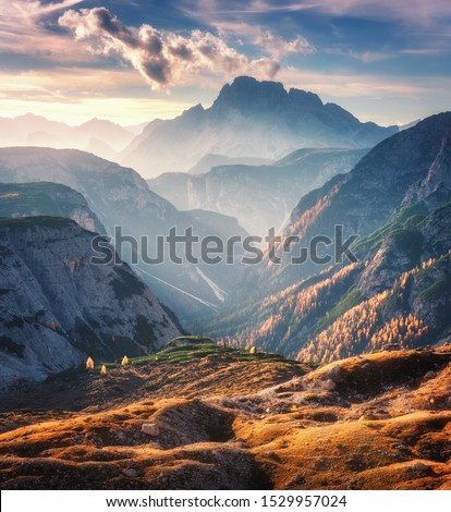 Mountain canyon lighted by bright sunbeams at sunset in autumn in Dolomites, Italy. Landscape with mountain ridges, rocks, colorful trees and orange grass, alpine meadows, gold sunlight in fall. Alps #1529957024