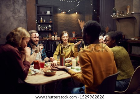 Group of young friends playing guessing game while sitting at table during dinner party in dark room, copy space #1529962826