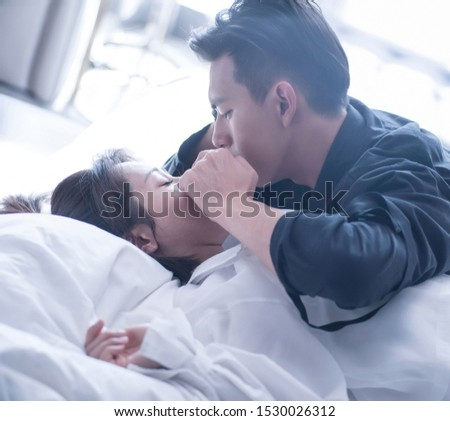 Shanghai, China- October 6,2019: A young Asian man is hugging his girlfriend on bed #1530026312