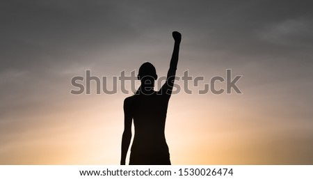 Strong, victorious , and motivated young woman raising her fist up to the sunset sky. Determination and overcoming adversity concept. Royalty-Free Stock Photo #1530026474