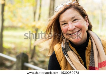 candid potrait of happy middle age woman hiking outdoors in autumn #1530050978