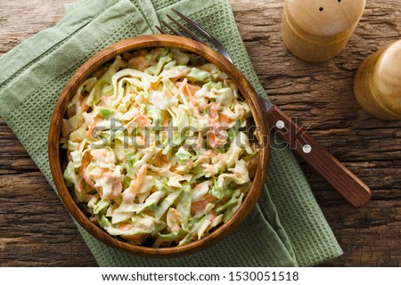 Coleslaw made of freshly shredded white cabbage and grated carrot with homemade mayonnaise-based salad dressing in wooden bowl, photographed overhead (Selective Focus, Focus on the salad) #1530051518