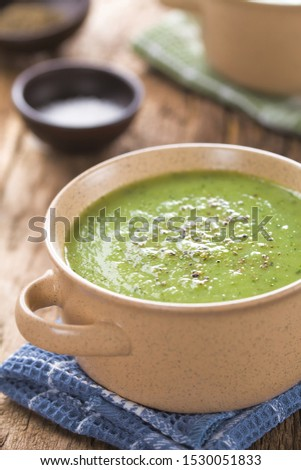 Fresh homemade cream of zucchini soup garnished with freshly ground black pepper served in bowls (Selective Focus, Focus one third into the soup) #1530051833