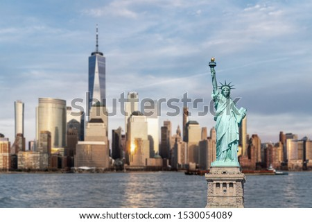 Statue of Liberty with background of New York city Manhattan skyline cityscape at sunset from New Jersey.  #1530054089