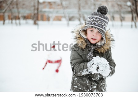 Cheerful child with a snowball playing in the winter Park. #1530073703