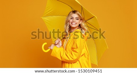 young happy emotional cheerful girl laughing  with umbrella   on colored yellow background #1530109451