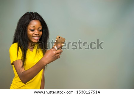 satisfied Young African hipster girl,types text message on cell phone, enjoys online communication, types feedback, wears yellow shirt, isolated on Gray studio wall. Technology concept #1530127514