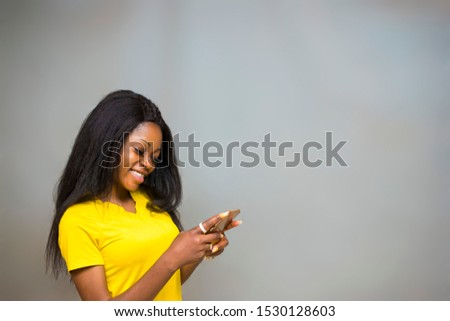 satisfied Young African hipster girl,types text message on cell phone, enjoys online communication, types feedback, wears yellow shirt, isolated on Gray studio wall. Technology concept #1530128603