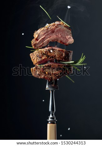 Grilled ribeye beef steak with rosemary on a black background. Beef steak on a fork sprinkled with rosemary and sea salt.    #1530244313