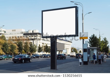 Horizontal digital banner near bus stop on busy road in city center. Drivers, passengers and pedestrians looking at commercial ads on billboard with big screen. Highway with several lanes, street lamp