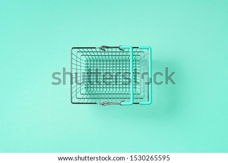 Top view of supermarket shopping basket on trendy green background. Black friday sale concept. Copy space. Sustainable lifestyle #1530265595