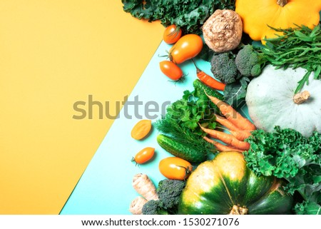 Autumn vegetables on trendy yellow and green background. Top view. Vegan and vegetarian diet, harvest concept. Ingredients for cooking - pumpkin, tomatoes, cucumber, pepper, kale, broccoli, celery. #1530271076