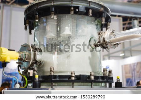 Industrial pneumatic conveying system for bulk solids. Transparent container for collecting plastic granules. Various pipelines are connected to the tank. Royalty-Free Stock Photo #1530289790