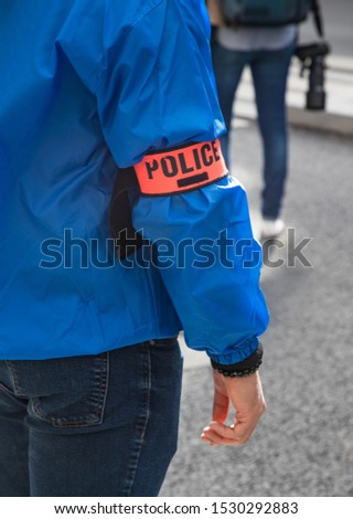 Close up on French police officer wearing police identification armband on the streets of Paris