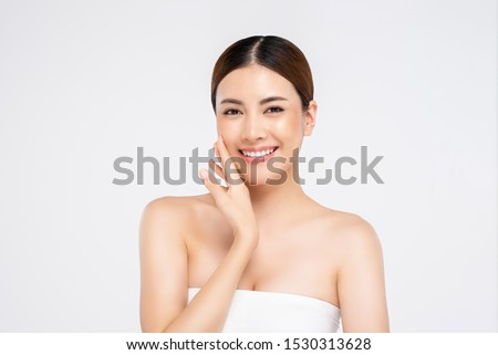 Youthful radiant pretty Asian woman with hand touching face on white background for beauty and skin care concepts Royalty-Free Stock Photo #1530313628