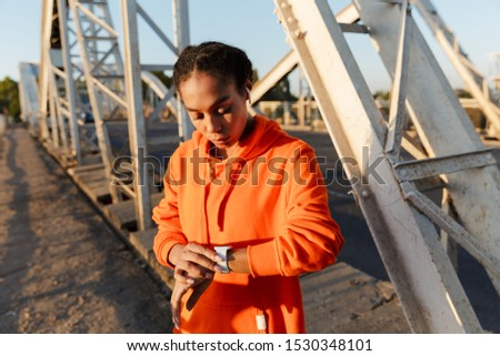 Photo of african american young woman in sportswear using earpods and smatwatch while working out on old bridge #1530348101