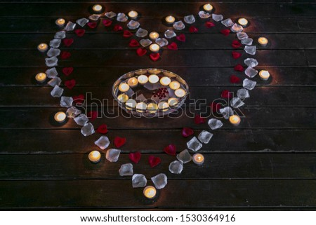 Tealight candles in a shape of a heart, shallow focus photo. Valentines candles burning at night. Many burning candles with shallow depth of field.  #1530364916