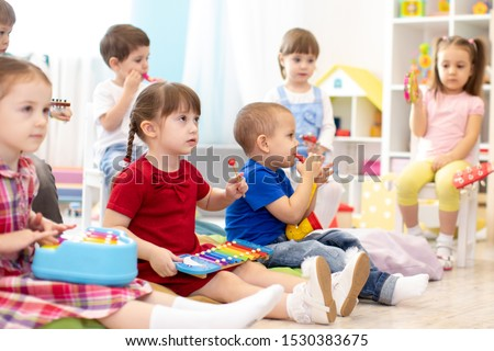 Music lesson for group of children in kindergarten or kids centre Royalty-Free Stock Photo #1530383675
